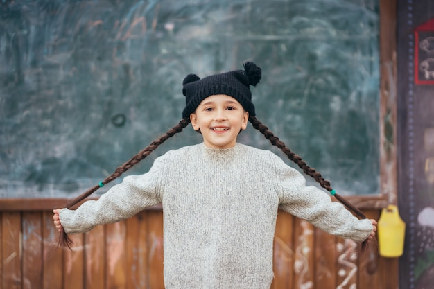 Menina de chapéu posando no fundo da lousa de escola