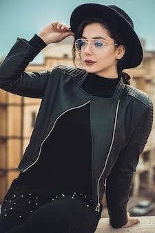 Menina de chapéu preto e jaqueta de couro