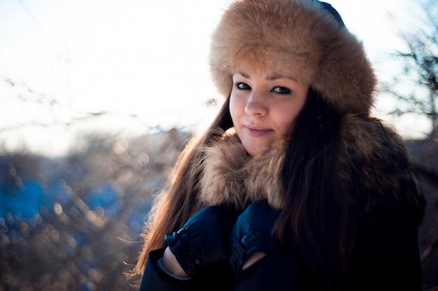 Menina de chapéu quente com abas de orelha no fundo da neve