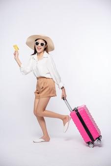 Menina de chapéu segurando um cartão de crédito e uma mala para viajar