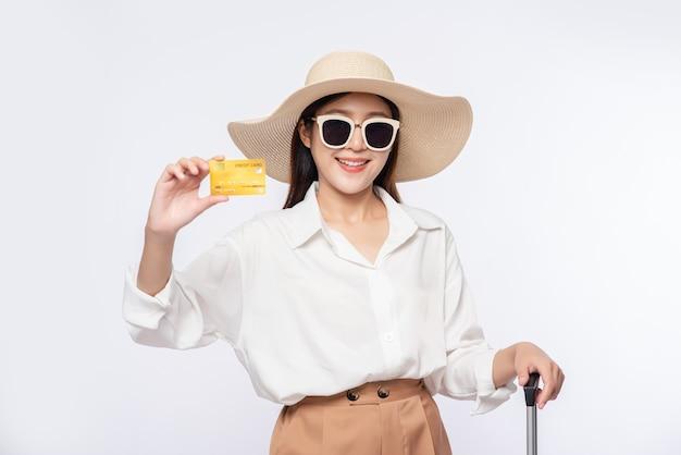 Menina de chapéu segurando um cartão de crédito e uma mala para viajar Foto gratuita