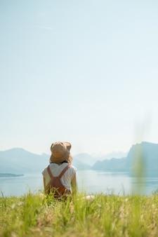 Menina de chapéu sentada em um gramado verde perto do lago