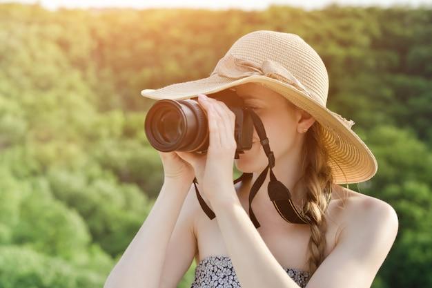 Menina de chapéu tira fotos na floresta verde. vista lateral