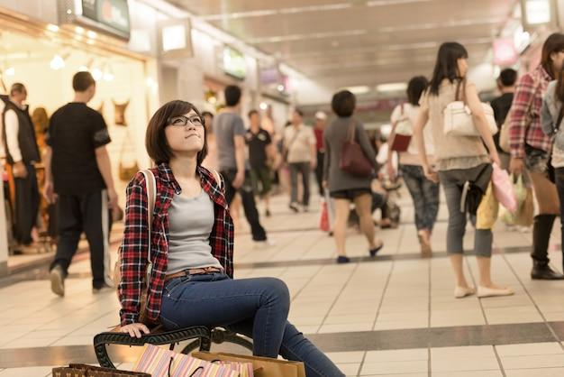 Menina de compra asiática sentar na cadeira e descansar na rua em taipei, taiwan.