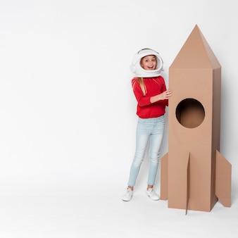 Menina de cópia-espaço brincando com nave espacial