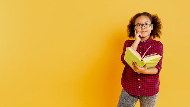 Menina de cópia-espaço com óculos lendo