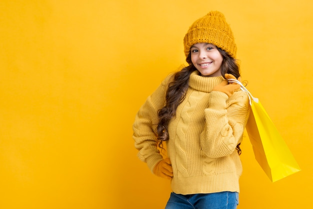 Menina de cópia-espaço com saco de roupas de compras de inverno