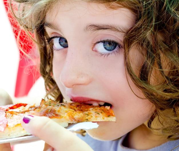 Menina de criança de olhos azuis comendo fatia de pizza