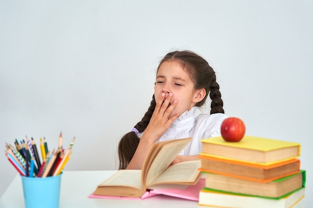 Menina de criança menina sentada em uma mesa e bocejando. escola cansada e lição de casa.