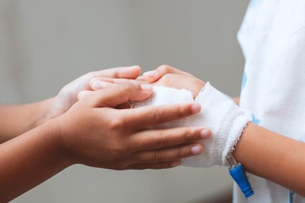 Menina de criança segurando a mão da irmã jovem doente que têm solução iv enfaixada com amor e cuidado