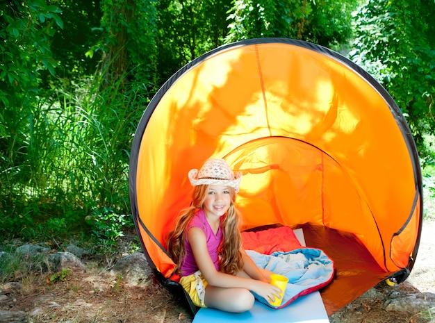 Menina de crianças acampando com chapéu na tenda da floresta ao ar livre