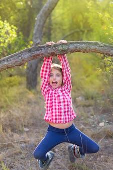 Menina de crianças balançando em um tronco na floresta de pinheiros