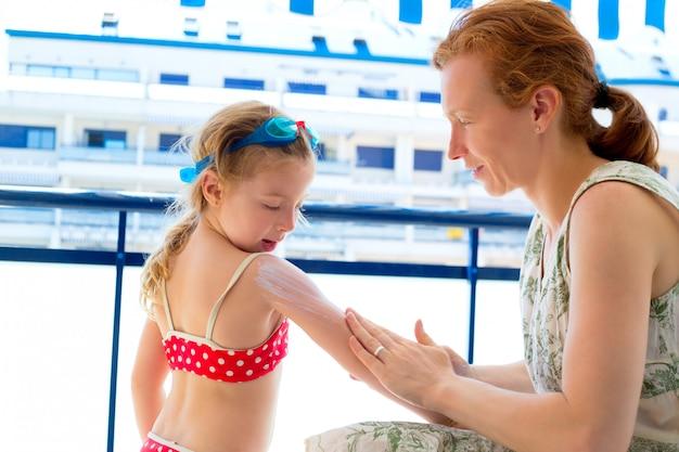 Menina de crianças com mãe aplicar protetor solar
