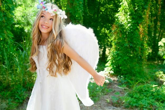 Menina de crianças de anjo de braços abertos nas asas de floresta branca