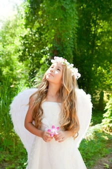 Menina de crianças de anjo segurando flor na mão, olhando o céu