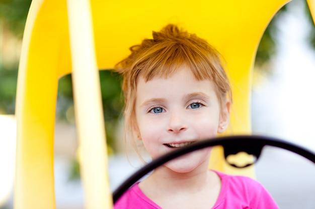 Menina de crianças loiras dirigindo carro de brinquedo