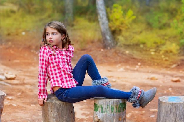 Menina de crianças relaxado em um tronco de árvore na floresta