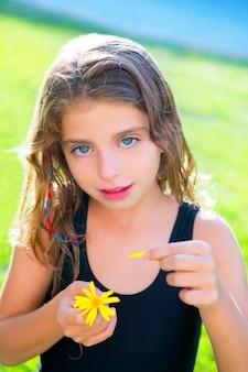 Menina de crianças testando o amor com pétalas de flor margarida amarela