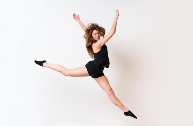 Menina de dança jovem sobre parede branca isolada