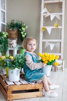 Menina de dois anos com buquê de tulipas amarelas