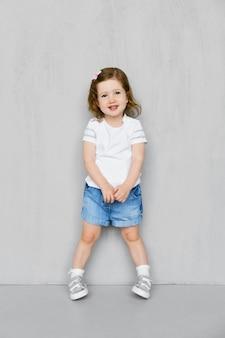 Menina de dois anos de idade em shorts jeans e t-short posando no estúdio