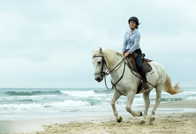 Menina de equitação e cavalo na praia