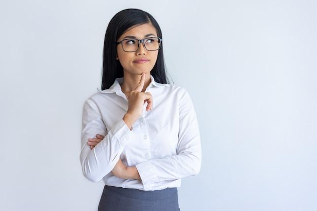 Menina de escritório chinesa pensativa que estuda a informação nova