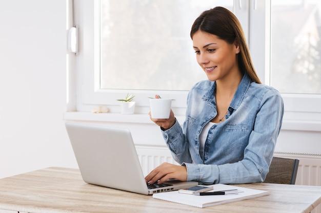 Menina de escritório feliz na mesa trabalhando no laptop