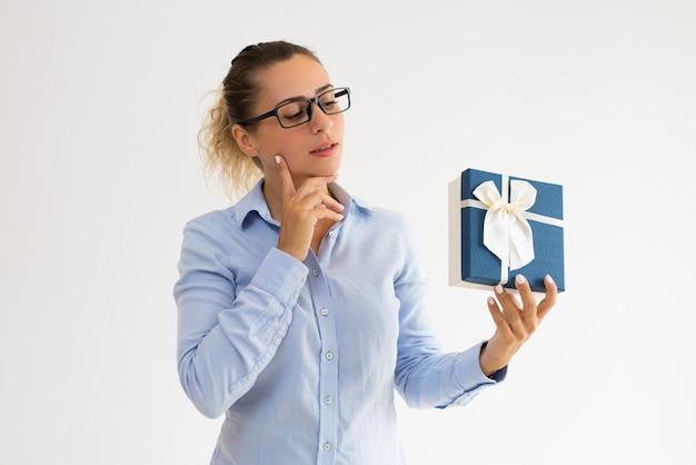 Menina de escritório pensativa em óculos adivinhando o que na caixa de presente