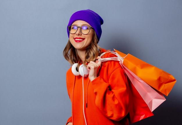 Menina de estilo com capuz laranja e chapéu roxo com sacos de compras na parede cinza