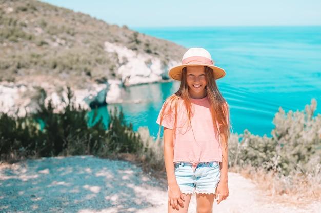 Menina de férias viaja com bela praia no fundo