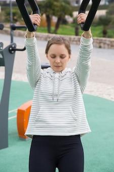 Menina de fitness concentrado exercitando com correias de suspensão