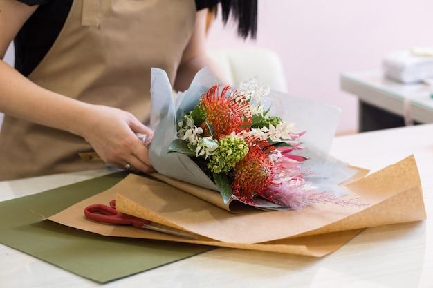 Menina de florista no avental de areia no trabalho cria um buquê de proteas