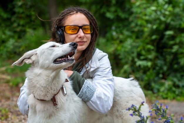 Menina de fones de ouvido e óculos abraça um cachorro.