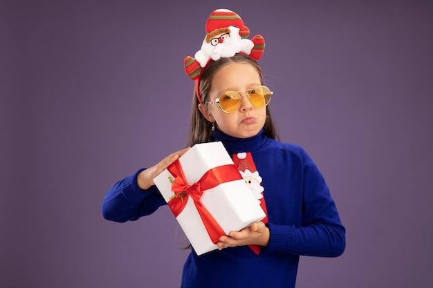 Menina de gola alta azul com gravata vermelha e aro de natal engraçado na cabeça segurando um presente olhando para a câmera com expressão triste franzindo os lábios em pé sobre um fundo roxo
