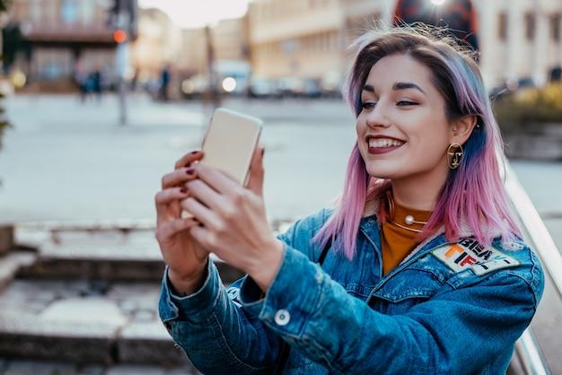 Menina de hipster sorridente tomando selfie na rua da cidade.