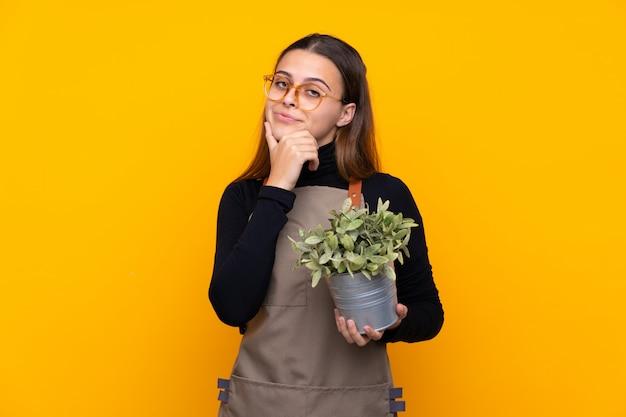 Menina de jardineiro isolado parede amarela