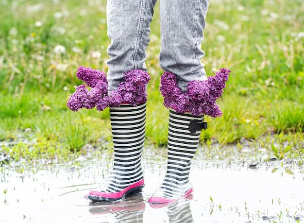 Menina de jeans e botas de borracha listradas com um buquê de flores lilás frescas em uma poça entre a grama.
