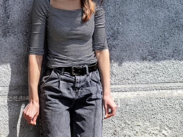 Menina de jeans preto e camiseta listrada perto da parede em tempo de sol