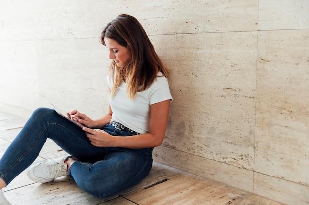 Menina de jeans, verificando o tablet moderno