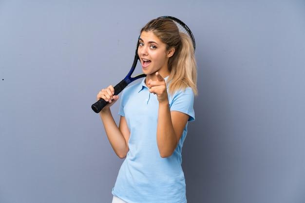 Menina de jogador de tênis adolescente sobre parede cinza surpreso e apontando a frente