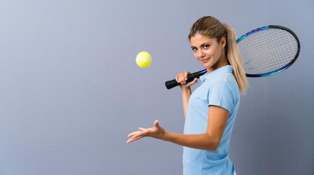 Menina de jogador de tênis adolescente sobre parede cinza
