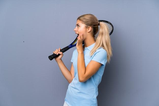 Menina de jogador de tênis de adolescente sobre gritos de parede cinza com a boca aberta
