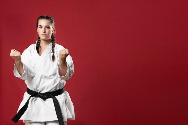 Menina de karatê de artes marciais com faixa preta e fundo de espaço de cópia