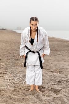 Menina de karatê tiro completo em traje de artes marciais