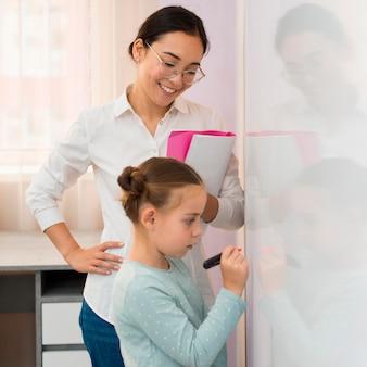 Menina de lado escrevendo em um quadro branco ao lado da professora