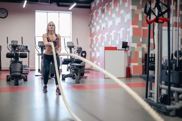 Menina de luta de cordas no ginásio treino exercício equipado corpo