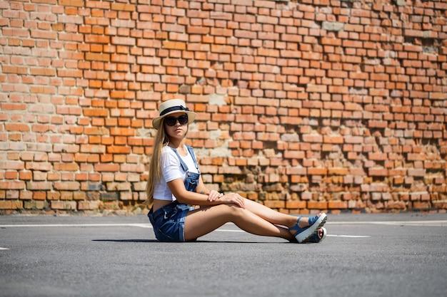 Menina de macacão jeans, uma camiseta branca e um chapéu claro no fundo de um prédio de tijolos sob o sol forte