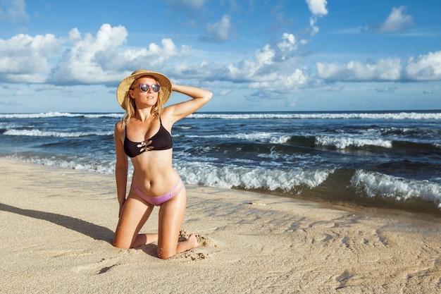 Menina de maiô e chapéu na praia e olhando bem