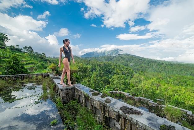Menina de maiô no místico hotel podre abandonado em bali, com céu azul.